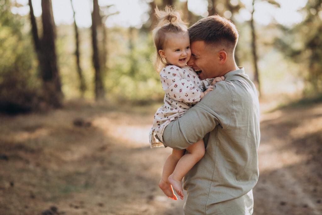papá con niña pequeña en brazos jugando en el bosque