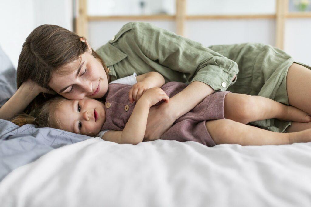 mamá y niña abrazadas en la cama